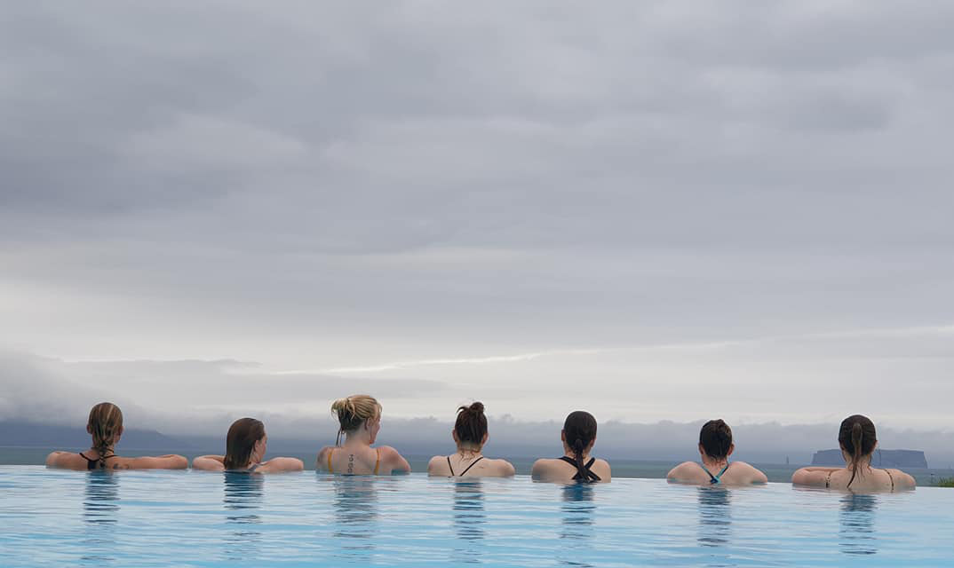 Seven women in a row in an outdoor swimming pool facing away from us