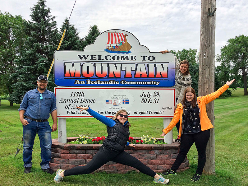 four past participants posing with the sign for Mountain, North Dakota